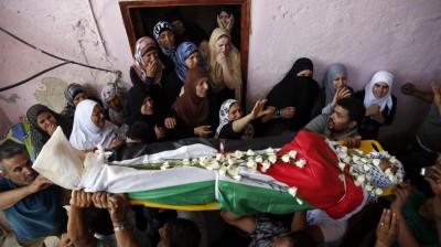Палестинцы несут тело Джихада Аслана во время похорон в лагере беженцев Каландия недалеко от города Рамалла на Западном берегу реки Иордан, 26 августа 2013