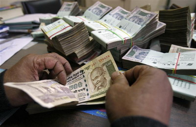 An employee counts Indian rupee notes at a cash counter inside a bank in Agartala