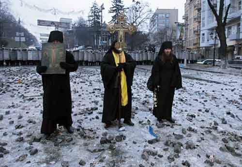 Священники молятся между полицейскими кордонами и протестующими