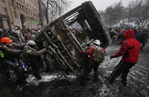 Протестующие переворачивают сгоревший автобус