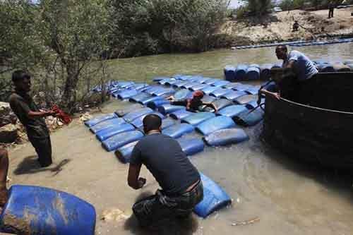 Группа мужчин тайно переправляет дизельное топливо из Сирии в Турцию надеясь продать его по более высокой цене. Река Аль-Асси в городе Даркуш, пригород Идлиба, 26 мая 2013.