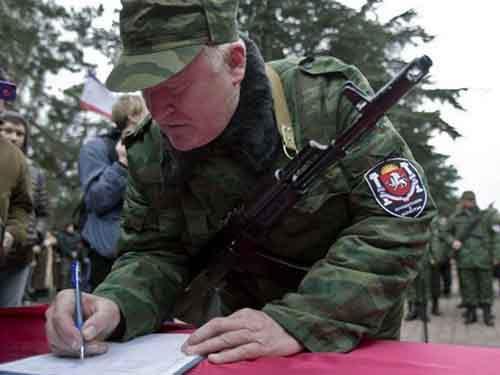 Вооружённый член первого подразделения пророссийских вооружённых сил подписывает клятву во время церемонии приведения к присяге в Симферополе.