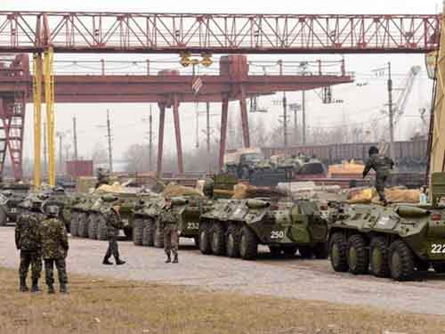Украинские солдаты производят погрузку своих бронетранспортёров (БТР) на железнодорожные платформы в западноукраинском городе Львове.