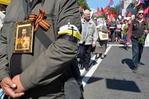 Пророссийский активист с георгиевской ленточкой, изображением русского царя Николая II и флагом бывшей Российской Империи принимает участие в шествии на праздновании Дня Победы в центре Киева.