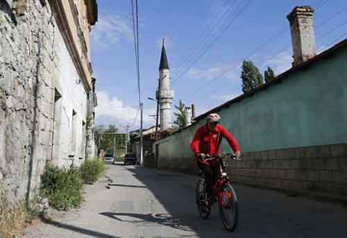 Велосипедист едет по улице Бахчисарая, исторической столицы крымских татар