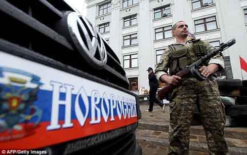 Вооружённый ополченец охраняет баррикады у захваченного здания областной администрации Луганска