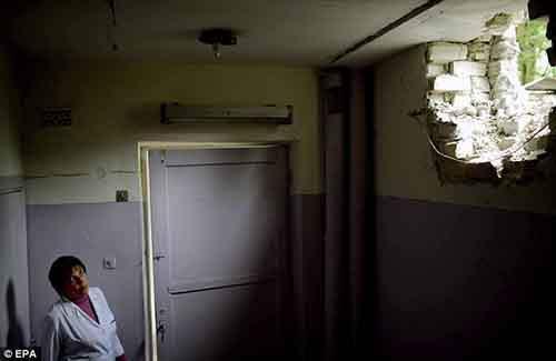 Женщина смотрит на пробоину в стене детской больницы