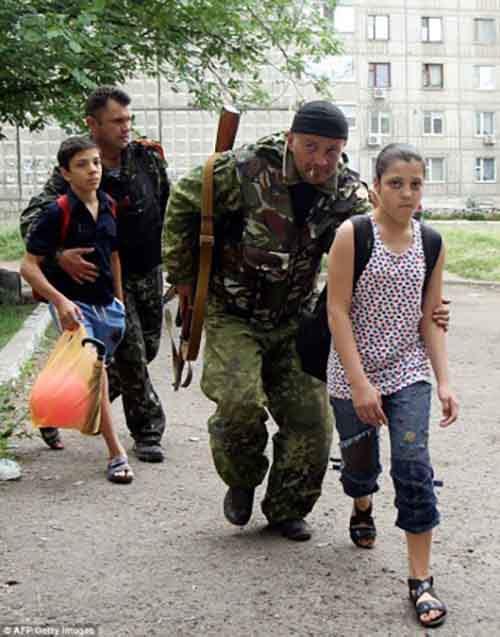 Ополченцы эвакуируют детей из близлежащих домов во время перестрелки