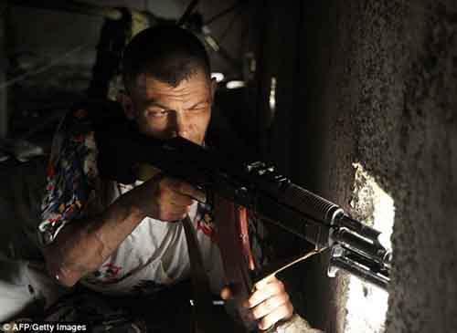 Пророссийский ополченец с чердака стреляет в пограничников, охраняющих здание управления пограничной службы в восточноукраинском городе Луганске