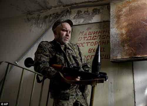 Пророссийский ополченец делает передышку, прежде чем подняться на крышу, чтобы вести оттуда огонь из РПГ