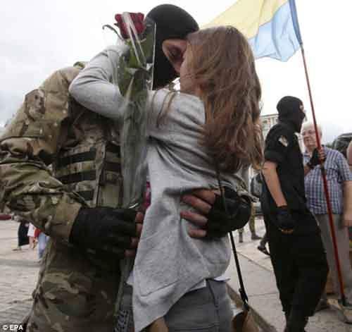 Подпись к изображению: Слёзное прощание: волонтёр-новобранец прощается с подругой после принятия присяги во время официальной церемонии, проходившей под Киевом