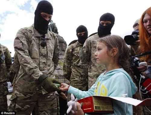 """Девочка угощает шоколадками новых добровольцев батальона """"Азов"""", в то время как по данным одного из членов парламента число погибших во время карательной операции детей в десять раз превышает официальные цифры"""