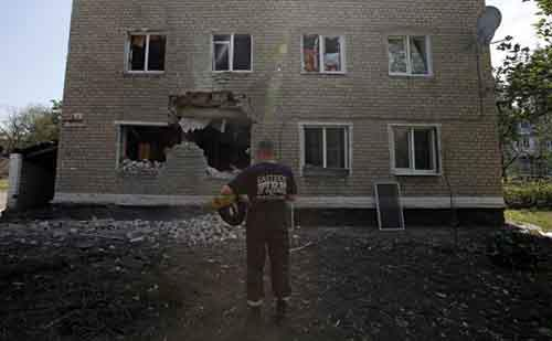Emergencies Ministry member looks at a damaged building following what locals say was recent shelling by Ukrainian forces in the settlement of Maryinka