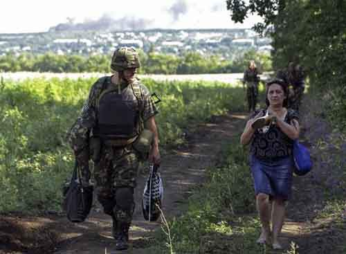 "Ukrainian army soldier from battalion ""Aydar"" helps a local resident as she leaves the village of Metalist near the eastern Ukrainian city of Luhansk"