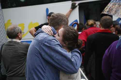 Residents of the Donetsk region in eastern Ukraine say farewell before boarding a bus for Rostov-on-Don in Russia from a collection point in Donetsk