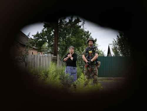 "A member of the Ukrainian police special task force ""Kiev-1"" stands beside a local woman in Semenovka"