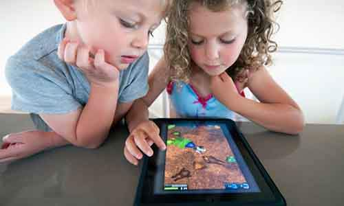 BY1HCB Children playing computer game on an iPad tablet computer