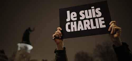 "A man holds a placard which reads ""I am Charlie"" to pay tribute during a gathering at the Place de la Republique in Paris"