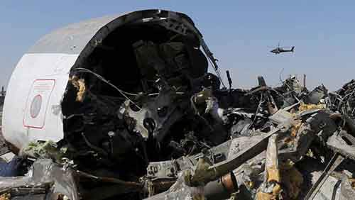 An Egyptian military helicopter flies over debris from a Russian airliner which crashed at the Hassana area in Arish city, north Egypt