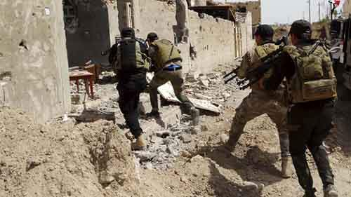 Iraqi security forces make their way during a patrol looking for Islamic State militants on the outskirts of Ramadi
