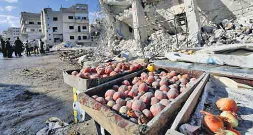 Produce are covered in dust as people inspect a site hit by what activists said were airstrikes carried out by the Russian air force on a busy market place in the town of Ariha, in Idlib province, Syria
