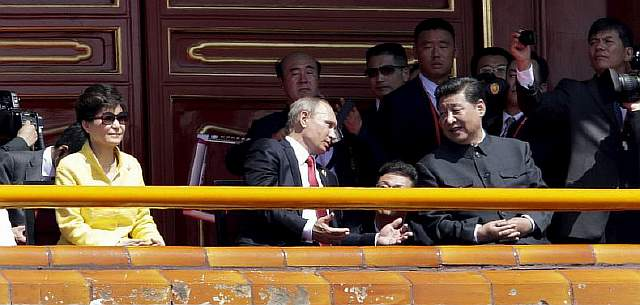 Russia's President Vladimir Putin chats with China's President Xi Jinping next to South Korea's President Park Geun-hye during the military parade in Beijing