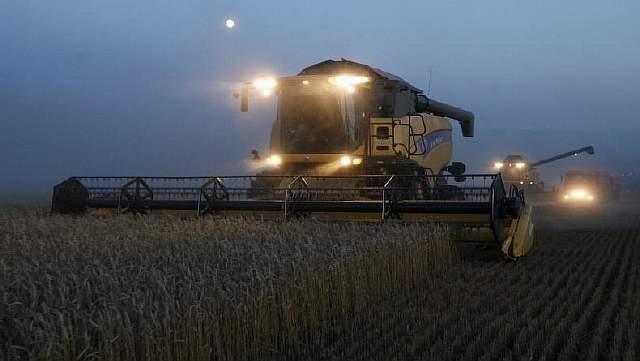 Зерноуборочные комбайны работают в темное время суток на пшеничном поле фермерского хозяйства «Солгонское» вблизи деревни Тальники к юго-западу от Красноярска, Россия, 27 августа 2015 года