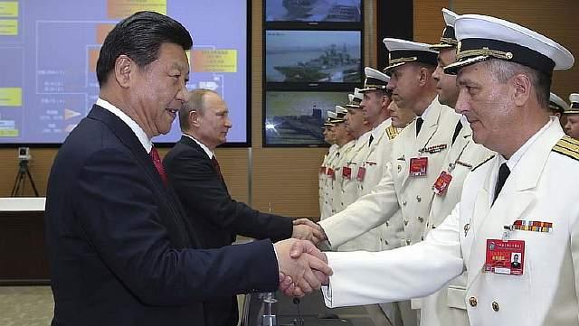 Подпись к изображению: Председатель КНР Си Цзиньпин и президент России Владимир Путин приветствуют участников совместных учений «Морское взаимодействие – 2014» в военном порту Усун в китайском Шанхае