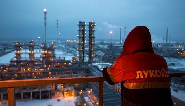 An employee looks out over the illuminated petroleum cracking complex at the Lukoil-Nizhegorodnefteorgsintez oil refinery, operated by OAO Lukoil, in Nizhny Novgorod, Russia, on Thursday, Dec. 4, 2014. Crude slumped 18 percent last month as the Organization of Petroleum Exporting Countries maintained its output quota, letting prices decrease to a level that may slow U.S. production. Photographer: Andrey Rudakov/Bloomberg via Getty Images