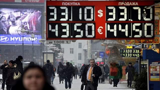 Подпись к изображению: Люди проходят мимо электронного табло с изображением курса доллара и евро рядом с одним из обменных пунктов в Москве, 2009 год