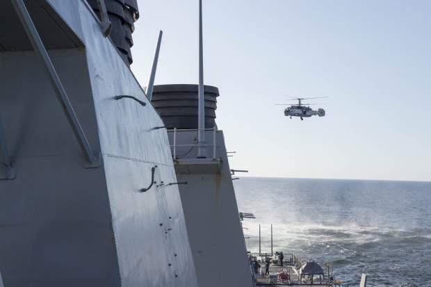 Подпись к изображению: На снимке, представленном ВМС США, российский вертолет Ка-27 совершает облет на низкой высоте американского ракетного эсминца Donald Cook (DDG 75) в момент его движения в международных водах 12 апреля 2016 года в Балтийском море. Эсминец осуществляет регулярное патрулирование в зоне действия 6-го Флота США в рамках обеспечения интересов национальной безопасности США в Европе