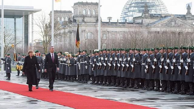 Подпись к изображению: Канцлер Германии Ангела Меркель с воинскими почестями приветствует в Берлине генерального секретаря НАТО Йенса Столтенберга, 14 января 2015 года