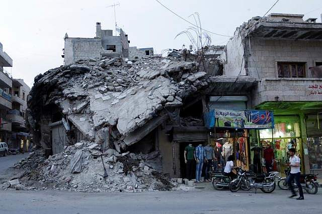 A clothing shop displays its merchandise beside a damaged building in the rebel-controlled area of Maaret al-Numan town in Idlib province, Syria, May 15, 2016. REUTERS/Khalil Ashawi