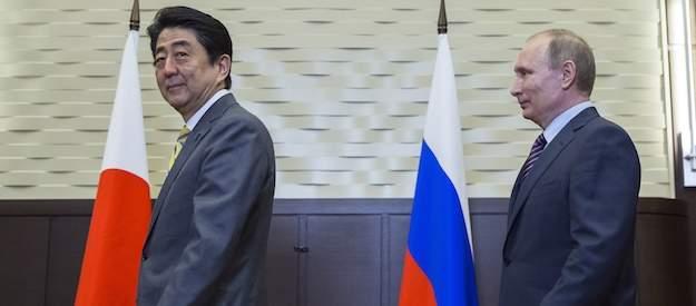 комментарий к изображению: президент России Владимир Путин и премьер-министр Японии Синдзо Абэ входят в зал во время встречи в Сочи, Россия, в пятницу, 6 мая 2016 года.