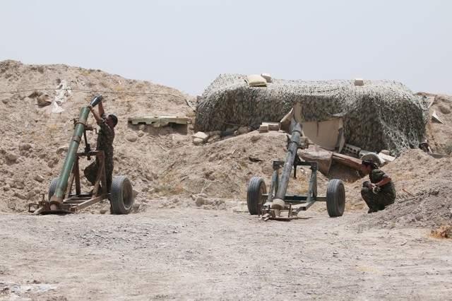 Подпись к изображению: Бойцы сирийских демократических сил готовятся к минометному обстрелу позиций ДАИШ в северной провинции Ракка, 27 мая 2016 года