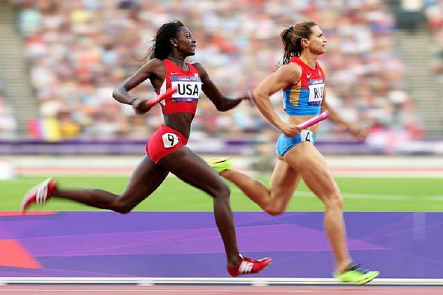 Подпись к изображению: Даймонд Диксон из США и Наталья Назарова из России состязаются на этапе женской эстафеты 4 по 400 метров во время Олимпийских Игр в Лондоне в 2012 году