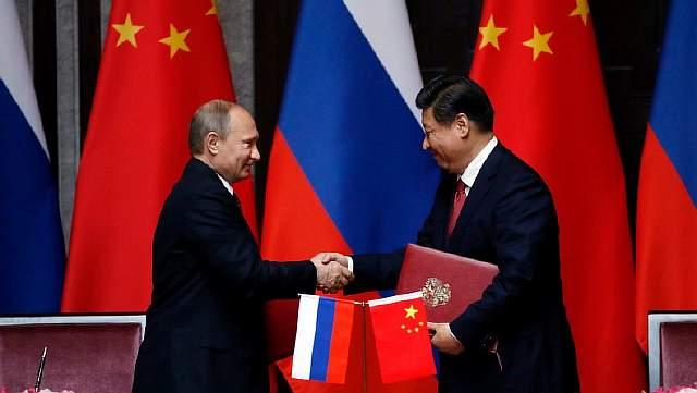 Подпись к изображению: Российский президент Владимир Путин и президент Китая Си Цзиньпин пожимают друг другу руки после подписания договора 20 мая 2014 года в Шанхае