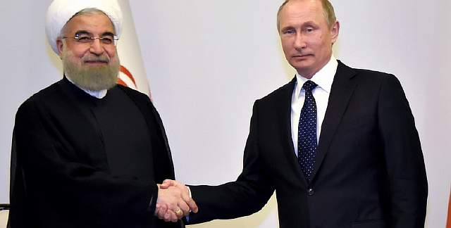 Russian President Vladimir Putin shakes hands with Iranian President Hassan Rouhani during their meeting in Baku