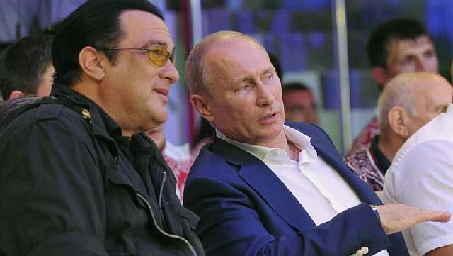 Подпись к изображению: Российский президент Владимир Путин и американский актер Стивен Сигал наблюдают за состязаниями на первом российском национальном чемпионате по боевым единоборствам в Сочи, 11 августа 2012 года