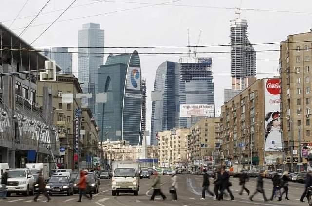 Подпись к изображению: Люди пересекают улицу на фоне Восточной башни комплекса «Москва-сити», апрель 2012 года
