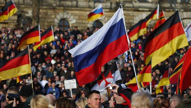 Supporters of the anti-Islam movement PEGIDA carry German and Russian flags during a demonstration in Dresden