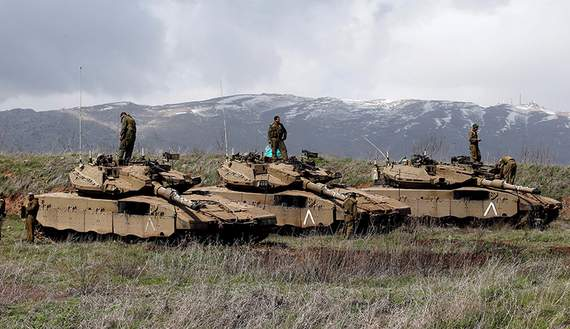 Israeli soldiers stand atop tanks in the Golan Heights near Israel's border with Syria March 19, 2014. REUTERS/Ronen Zvulun/File Photo - RTX2JLDC