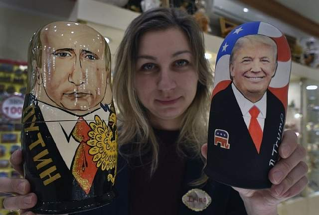 An employee displays traditional Russian wooden nesting dolls, Matryoshka dolls, depicting US President-elect Donald Trump (R) and Russian President Vladimir Putin at a gift shop in central Moscow on January 16, 2017, four days ahead of Trump's inauguration. / AFP PHOTO / Alexander NEMENOV