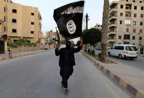 "A member loyal to the Islamic State in Iraq and the Levant (ISIL) waves an ISIL flag in Raqqa June 29, 2014. The offshoot of al Qaeda which has captured swathes of territory in Iraq and Syria has declared itself an Islamic ""Caliphate"" and called on factions worldwide to pledge their allegiance, a statement posted on jihadist websites said on Sunday. The group, previously known as the Islamic State in Iraq and the Levant (ISIL), also known as ISIS, has renamed itself ""Islamic State"" and proclaimed its leader Abu Bakr al-Baghadi as ""Caliph"" - the head of the state, the statement said. REUTERS/Stringer (SYRIA - Tags: POLITICS CIVIL UNREST TPX IMAGES OF THE DAY) (Newscom TagID: rtrlsix541650.jpg) [Photo via Newscom]"