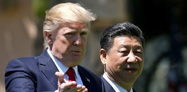 U.S. President Donald Trump and China's President Xi Jinping chat as they walk along the front patio of the Mar-a-Lago estate after a bilateral meeting in Palm Beach, Florida, U.S., April 7, 2017. REUTERS/Carlos Barria - RTX34M63