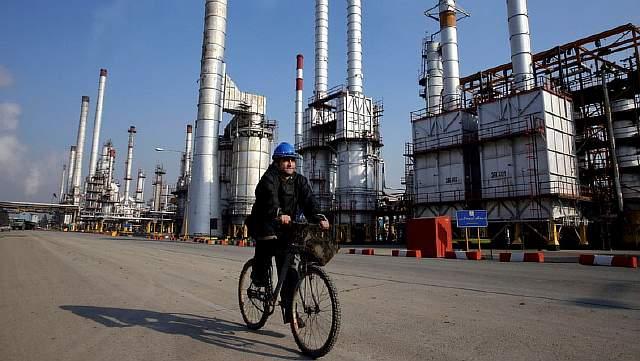 Подпись к изображению: Иранский нефтяник едет на велосипеде по территории нефтеперерабатывающего завода на юге Тегерана 22 декабря 2014 года.