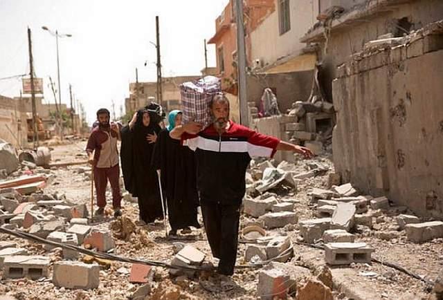 Подпись к изображению: На снимке от 15 мая 2017 года иракцы пробираются через руины, покидая зону военных действий, в которых участвуют спецподразделения Ирана и боевики ИГИЛ в иракском городе Мосул. Америка стремится полностью разгромить ИГИЛ, хотя местным вооружённым силам при поддержке США ещё предстоит уничтожить основные группировки террористов в Ираке и Сирии.