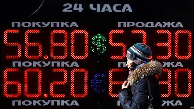 epa05794842 A woman passes a screen displaying foreign currency exchange rates outside a currency exchange office in Moscow, Russia, 15 February 2017. Russian ruble resumed its growth up from the previous exchange rates. The euro decreased to 60,02 rubles and dollar decreased to 56,77 rubles.  EPA/YURI KOCHETKOV