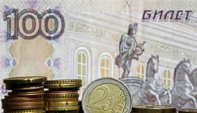 Монеты евро на фоне сторублевой купюры. 21 апреля 2015 года. Рубль стабилен к полудню четверга, сохраняя небольшой минус после роста на пятинедельный максимум накануне вечером в ответ на новость о приватизации части Роснефти, поскольку рынок не стремится играть против намерений российских регуляторов провести конвертацию полученной валюты за рубли без существенных колебаний курса. REUTERS/Dado Ruvic