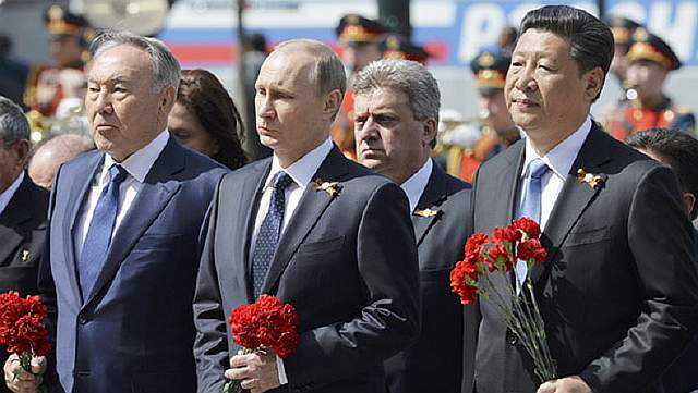 Russian President Vladimir Putin (C), Kazakhstan's President Nursultan Nazarbayev (L) and China's President Xi Jinping take part in a wreath laying ceremony at the Tomb of the Unknown Soldier on the Victory Day by the Kremlin walls in central Moscow, Russia, May 9, 2015. Russia marks the 70th anniversary of the end of World War Two in Europe on Saturday with a military parade, showcasing new military hardware at a time when relations with the West have hit lows not seen since the Cold War. REUTERS/Host Photo Agency/RIA Novosti ATTENTION EDITORS - THIS IMAGE HAS BEEN SUPPLIED BY A THIRD PARTY. IT IS DISTRIBUTED, EXACTLY AS RECEIVED BY REUTERS, AS A SERVICE TO CLIENTS